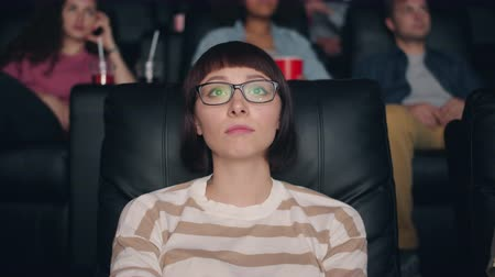 personalità : Pretty young girl in glasses is watching sad movie in cinema touching sensitive face looking at screen. Modern entertainment and human emotions concept.