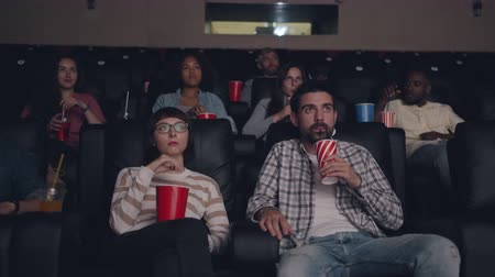 cibo etnico : People young friends are watching film in cinema drinking and eating snacks sitting in darkness together enjoying movie. Youth and entertainment concept.
