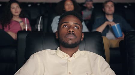 can sıkıntısı : Sleepy African American student bearded guy is watching movie in cinema closing eyes winking relaxing in comfortable seat. Youth and relaxation concept.