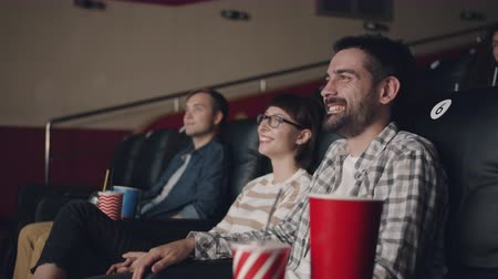 初演 : Slow motion of joyful girls and guys watching film in movie theater laughing having fun sitting on chairs indoors. Culture, leisure and youth concept.