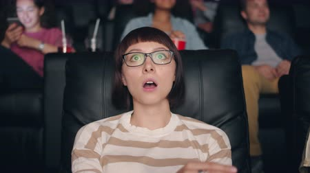 sensível : Slow motion of beautiful young woman in glasses watching shocking content in cinema opening mouth then touching face with hand sitting in seat alone.