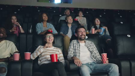 assistindo : Joyful young people men and womena are watching funny comedy in cinema laughing looking at screen in dark room. Emotions, fun and entertainment concept.