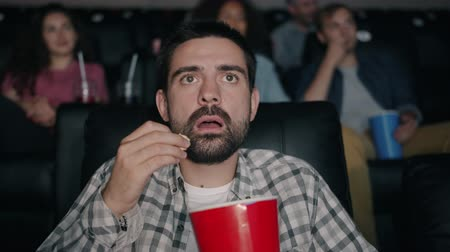 pipoca : Slow motion of shocked young man watching film in cinema with open mouth dropping popcorn looking at screen with attention. People and reaction concept. Stock Footage