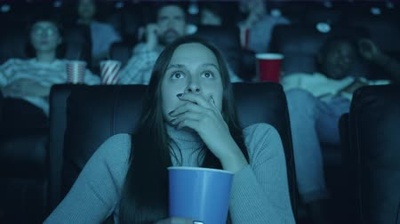 vay : Scared woman watching horror film with open mouth holding popcorn in cinema enjoying interesting movie among men and women. Youth and emotions concept.