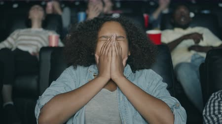 espectador : Slow motion of scared African American teenage girl watching horror film in cinema closing eyes sitting in dark hall. Youth, lifestyle and emotions concept.