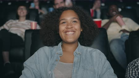 enjoyable : Portrait of happy African American teenager laughing watching film in cinema having fun enjoying comedy. Modern young people, lifestyle and entertainment concept.