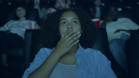 espectador : Slow motion of young pretty African American woman watching film in cinema with open mouth looking at screen with attention. Youth and emotions concept.