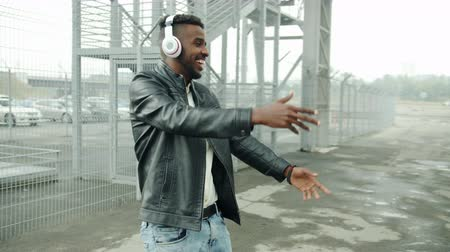 jó hangulatban : Slow motion of African American guy in headphones dancing outdoors against urban background having fun laughing. Youth and modern lifestyle concept.