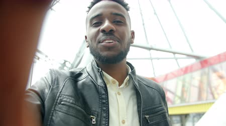 wi fi : POV slow motion shot of young African American man making online video call talking looking at camera outdoors standing near observation wheel. Vídeos