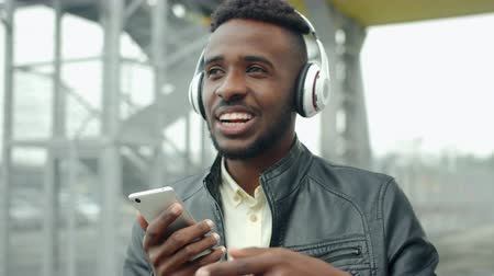 rapper : Cheerful African American man in headphones is singing using smartphone outdoors having fun alone in city street. Modern devices, lifestyle and fun concept.