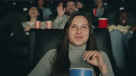 lachen : Slow motion of pretty brunette enjoying film in dark cinema laughing eating popcorn looking at screen with joyful face. People and entertainment concept.