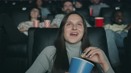 premiere : Cheerful young girl is laughing watching movie in cinema eating popcorn having fun sitting on armchair in dark room. Emotions, millennials and leisure concept. Stock Footage