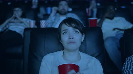 duyarlı : Slow motion portrait of beautiful young girl watching sad movie and eating popcorn in cinema feeling compassion and sadness. Youth and human emotions concept.