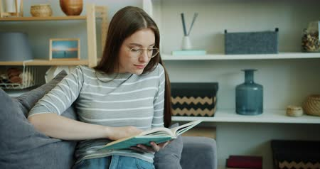 novel : Smiling young woman student is reading interesting book indoors in cozy light studio apartment. Smart lady is wearing casual clothing and trendy glasses.