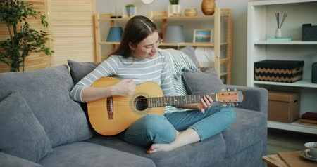 akusztikus : Beautiful young woman in glasses is playing the guitar sitting on sofa at home in lotus pose enjoying music and free time in apartment. People and skills concept.