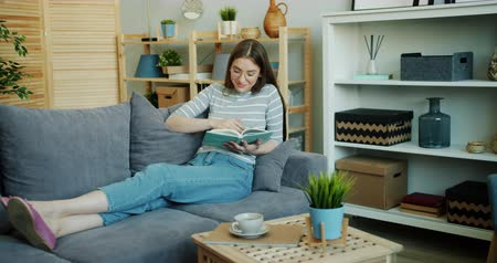 lezer : Beautiful girl student is reading book turning pages relaxing on sofa in apartment smiling enjoying novel. Modern lifestyle, people and hobby concept.