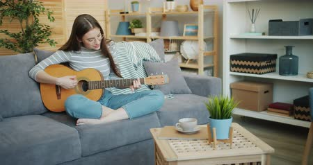 akusztikus : Slow motion of beautiful girl playing guitar at home having fun alone enjoying hobby and musical instrument. Youth, entertainment and lifestyle concept. Stock mozgókép