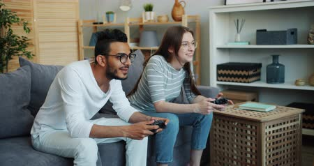 konsola : Girl and guy cute mixed race couple are enjoying video game at home using joysticks, woman is winning and celebrating success raising arms and laughing.