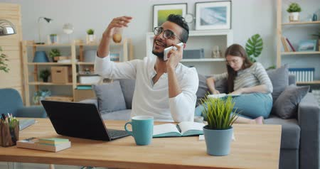 em casa : Slow motion of young Arab talking on mobile phone while Caucasian woman is reading in background. Conversation, business and family lifestyle concept. Stock Footage