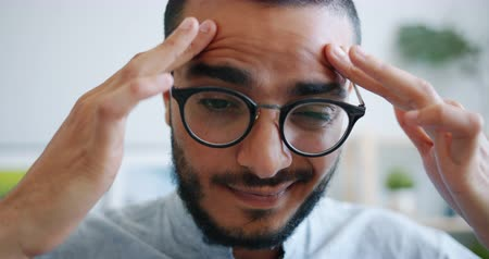 хмурый : Close-up portrait of unhappy young Arab in glasses touching head feeling headache massaging temples indoors at home. People, health and stress concept. Стоковые видеозаписи