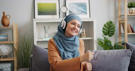 enjoyable : Modern Mulsim girl in headphones dancing enjoying music at home having fun sitting on couch alone in free time. People, lifestyle and youth culture concept.