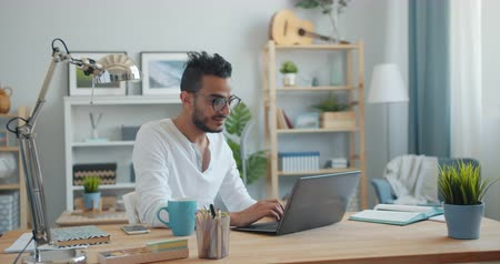 distante : Portrait of handsome young Arab using laptop at home then smiling looking at camera sitting at table alone. People, lifestyle and remote work concept.