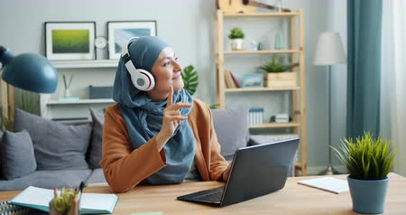 стремление : Joyful mixed race girl in hijab is enjoying music in headphones using laptop at home sitting at desk working with computer. People and lifestyle concept.
