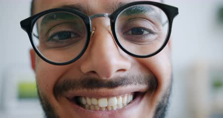 personalidade : Close-up portrait of handsome bearded Arabian man in trendy glasses looking at camera smiling indoors at home. People, individuality and youth concept.