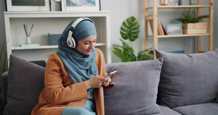 enjoyable : Cheerful Muslim girl in hijab is using smartphone and listening to music in modern headphones sitting on couch in apartment. Lifestyle and youth concept.