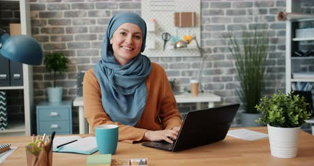 занятость : Portrait of beautiful Muslim girl in hijab smiling looking at camera in office at desk using laptop working. Modern people, lifestyle and business concept.