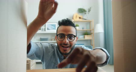 enjoyable : Slow motion of young Arab in glasses opening carton box taking present smiling enjoying gift indoors in apartment. Youth, surprises and emotions concept.