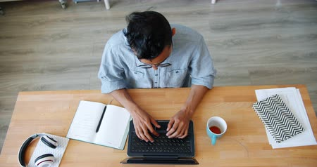 etkinlik : High angle view of African American man using laptop typing in office room sitting at desk alone concentrated on work. People, devices and workplace concept.