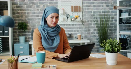 стремление : Attractive young woman in hijab is working in loft style office with laptop then smiling looking at camera. Modern devices, people and business concept.