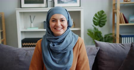 identité : Slow motion portrait of Middle Eastern woman in hijab looking at camera and smiling sitting on sofa at home alone. Beautiful people, emotions and houses concept.