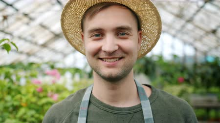 looking : Close-up portrait of handsome young gardener in hat and apron in greenhouse smiling looking at camera. Happiness, people and lifestyle concept.