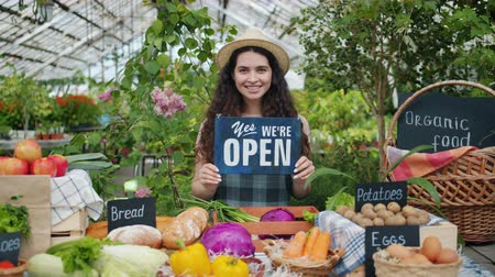 retailing : Portrait of pretty saleswoman holding open sign in farm market smiling looking at camera standing alone near table with organic fruit and vegetables. Business and lifestyle concept.