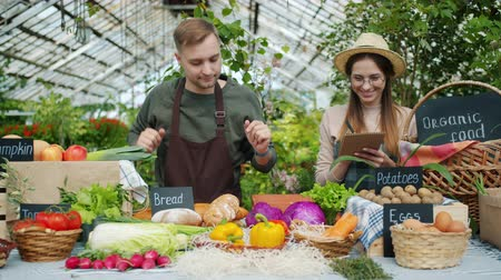 retailing : Cheerful young people farmers are putting organic food on table at farm sales talking smiling writing in notebook. Youth, small business and agriculture concept. Stock Footage