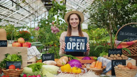 užitečný : Pretty girl in apron and hat holding open sign in organic food market smiling looking at camera standing near table with fruit and vegetables. People and shopping concept. Dostupné videozáznamy