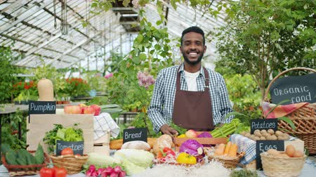 retailing : Portrait of cheerful African American salesman selling organic food in farm market standing at table smiling looking at camera. Business, people and nutrition concept.