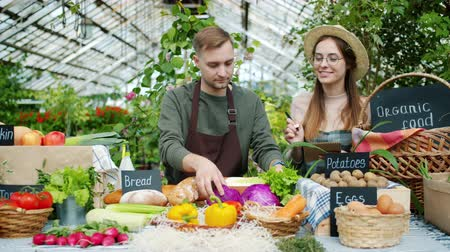 retailing : Girl and guy happy farmers are talking putting organic food on table during greenhouse sale. Modern people, small business and healthy nutrition concept. Stock Footage