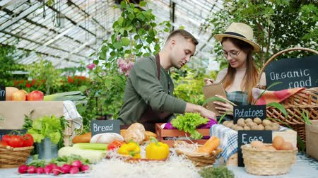 retailing : Sales people young man and woman are talking during organic food sale in greenhouse, fresh fruit and vegetables visible on table. Business and healthy nutrition concept.