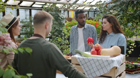 retailing : Slow motion of young people customers choosing organic vegetables in farm market indoors smelling touching food talking to salespeople. Healthy lifestyle concept. Stock Footage