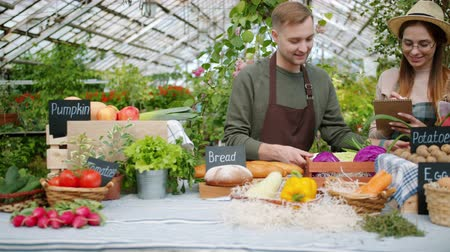 продавщица : Guy young successful farmer is bringing box of fresh organic vegetables to farm market talking to sales girl in greenhouse. Farming and business concept.