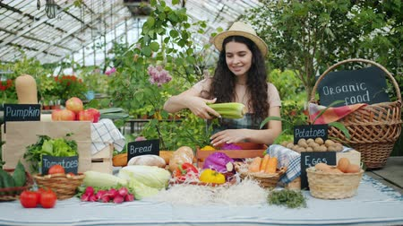 retailing : Happy female farmer in apron putting organic food on table in market smiling getting ready for autumn sale. People, business and healthy nutrition concept. Stock Footage