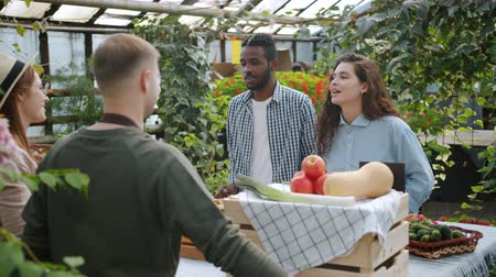 retailing : Young gardeners man and woman are talking to customers in farm market in greenhouse selling organic food. Modern business, agriculture and healthy lifestyle concept.