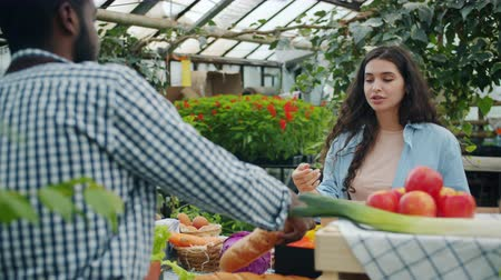 cortes : Young lady choosing organic food in farm market and talking to African American guy salesman. Communication, small business and healthy nutrition concept.