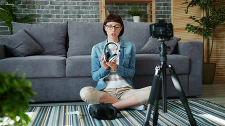 fikirler : Slow motion of attractive girl recording video about wireless headphones talking holding modern device using camera at home. Youth and blogging concept. Stok Video