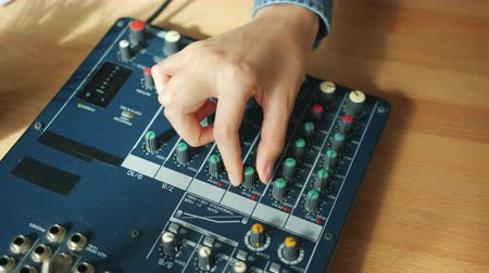 ajustando : Close-up of female hand adjusting sound quality recording podcast in studio touching buttons on panel. People, modern technology and work concept.