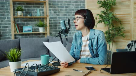 költő : Portrait of creative young lady recording podcast in microphone speaking holding paper with speech working at home alone. People and modern lifestyle concept. Stock mozgókép