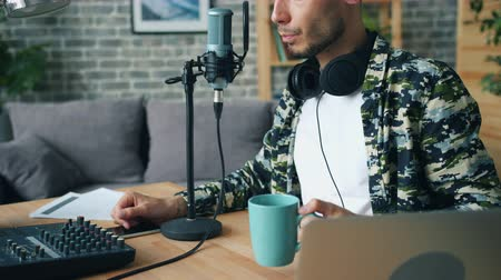 блог : Young guy blogger is drinking coffee and talking in microphone making podcast at home sitting at desk alone. Occupation, lifestyle and modern people concept. Стоковые видеозаписи